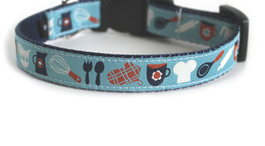 The In the Kitchen Dog Collar in light blue with a white chef's hat, orange plaid oven mitt, a whisk, and navy blue coffee mug and pitcher on navy blue webbing.