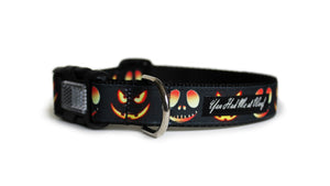 The front of the Jack O Lanterns Dog Collar in all black with glowing pumpkin faces with spooky expressions.