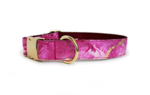 The Lovey Dog Collar with a gold buckle and pink and light pink marbling with gold flecks atop deep burgundy webbing.