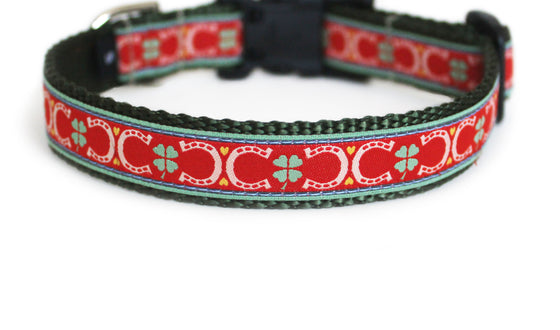 The Lucky Dog Collar in red with green four leaf clovers, and golden hearts and horseshoes atop olive green webbing.