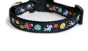 The Outer Space Dog Collar in black with navy blue trim, charming rocket ships, planets, an alien in a spaceship, and an astronaut.