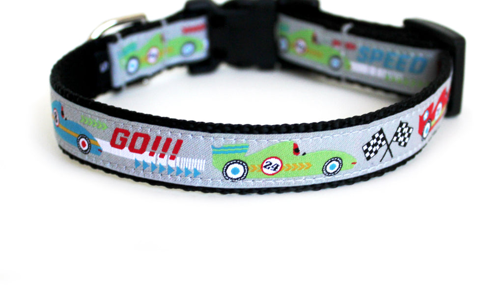 The Little Speedster Dog Collar in light gray with red, lime green, and light blue race cars, and checkered flags.