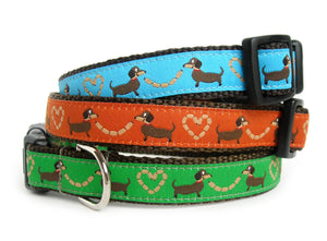 The Sausage Dogs Collar in brown webbing with your choice of blue, orange, green, white or red trim with brown sausage dogs holding sausage links in the shape of hearts.