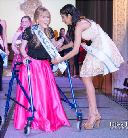 Miss Colorado handing a sash to Miss Passionate at The Serenity Project fashion show