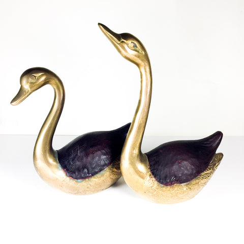 Pair of brass swans with leather accents