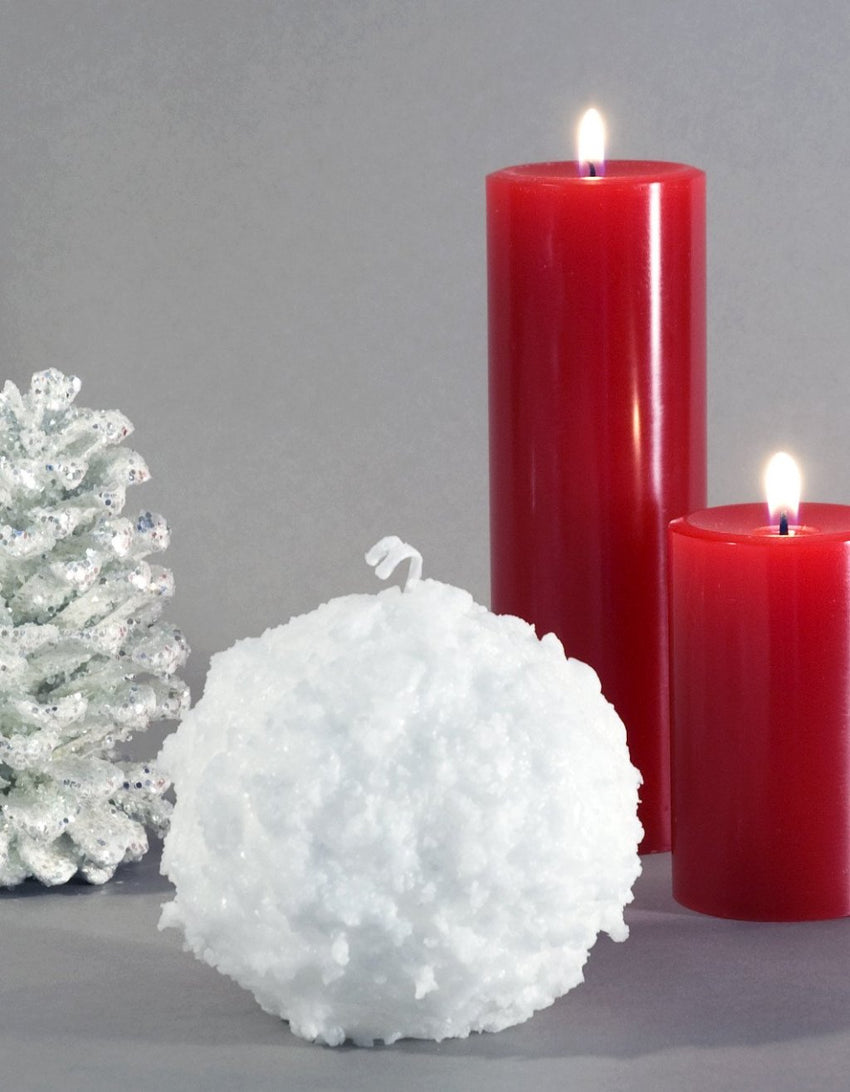 "Snowball Candle 3"" white with bumpy texture and two red pillar candles in background by Nordic Candle"