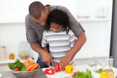 father helping kid cut vegetables in the kitchen