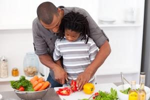 father helping child cut vegetables
