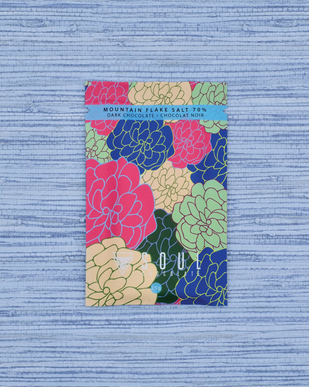The front of our Mountain Flake Salt 70% Dark Chocolate Bar has a fun floral pattern, representing the mixing of flavours (which you'll find in this bar).