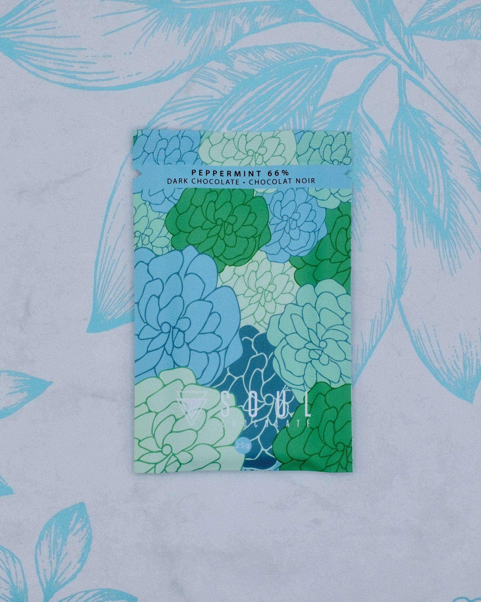 The front of our Peppermint 66% Dark Chocolate bar contains a fun floral pattern with colours that remind us of winter.
