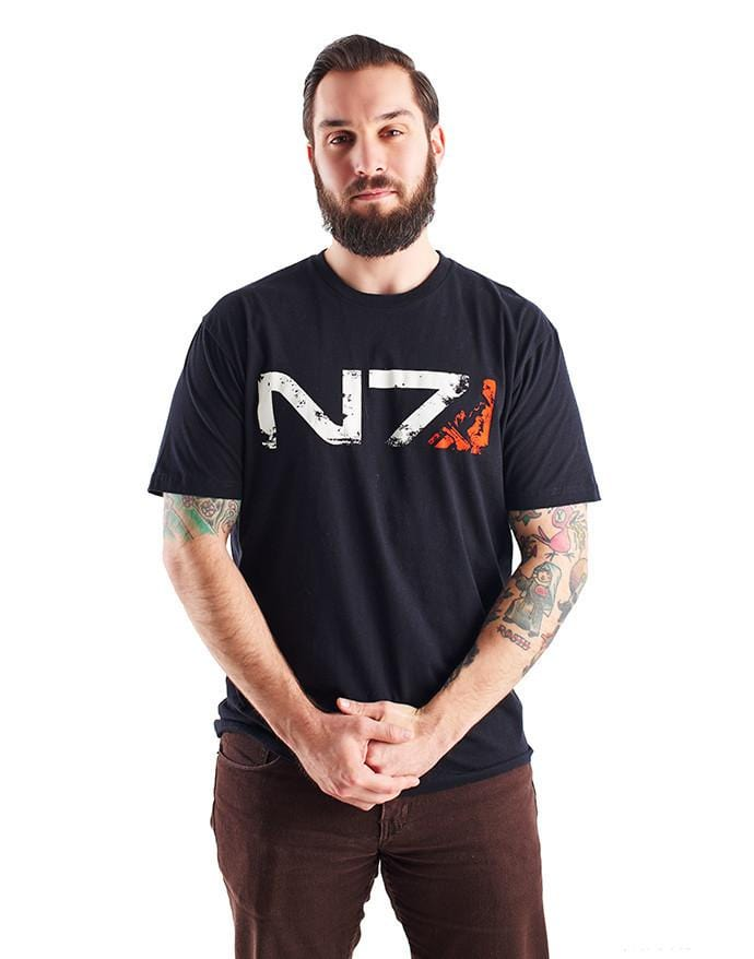 An image of the N7 Commander M-Shep Shirt. It is a black shirt with the N7 logo across the front in weathered-looking print, with m-Shep's face silhouetted in the red portion at the end.