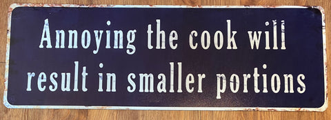 """Annoying the cook will result in smaller portions"" blue metal sign"