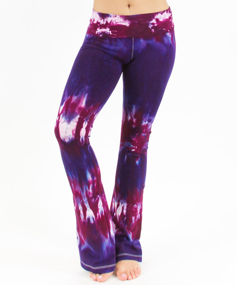 Woman wearing a pair of purple and pink tie dye yoga pants with a fold over waistband.