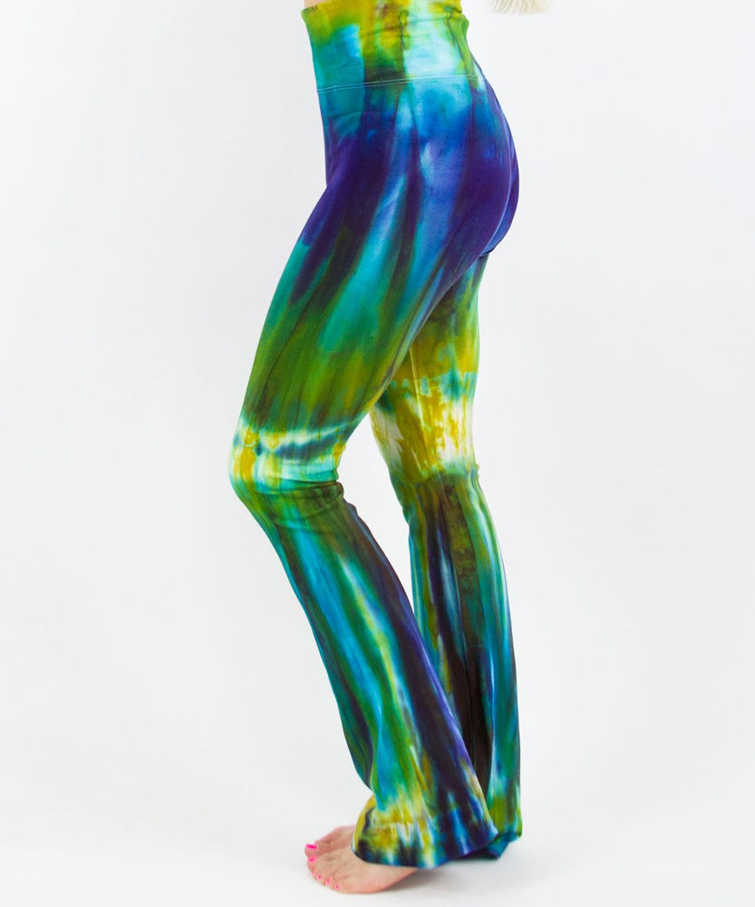 Woman wearing a navy blue and green tie dye yoga pants featuring a fold over waistband.