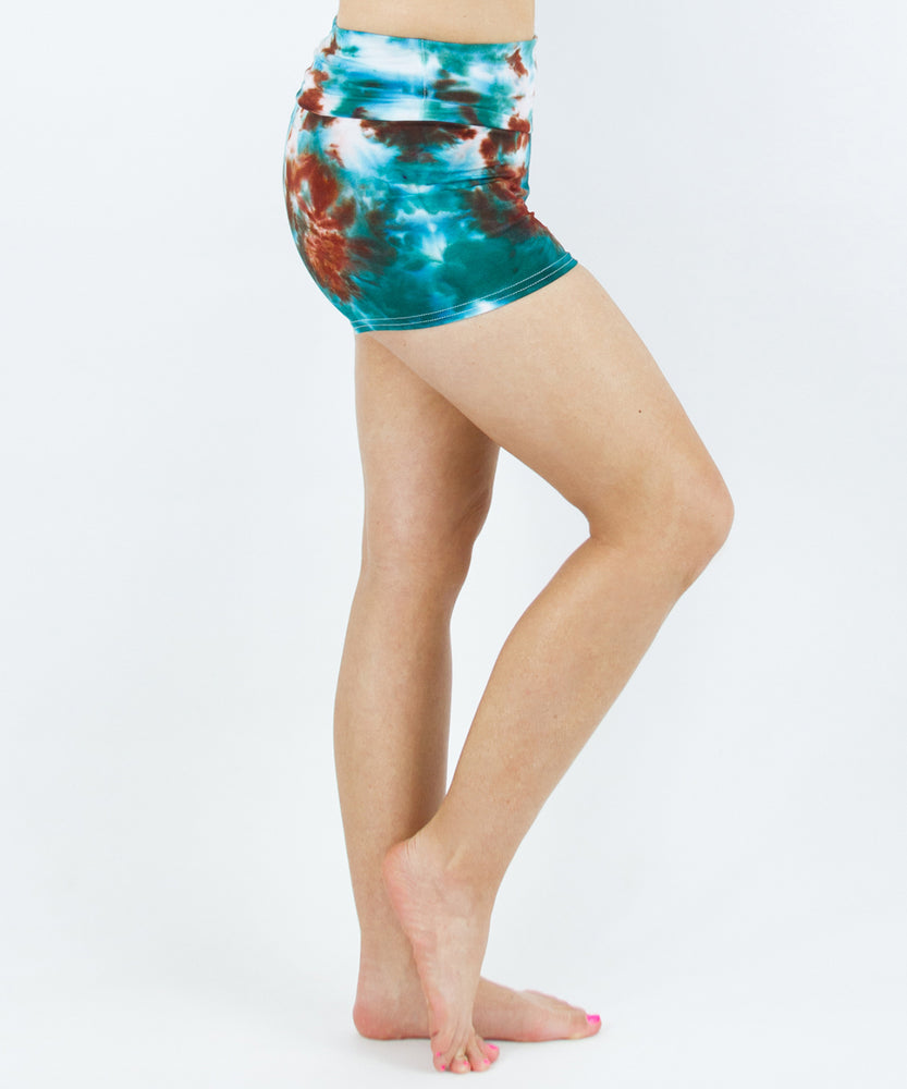 Woman wearing tie dye fold over shorts in the colors teal and bronze by Akasha Sun.