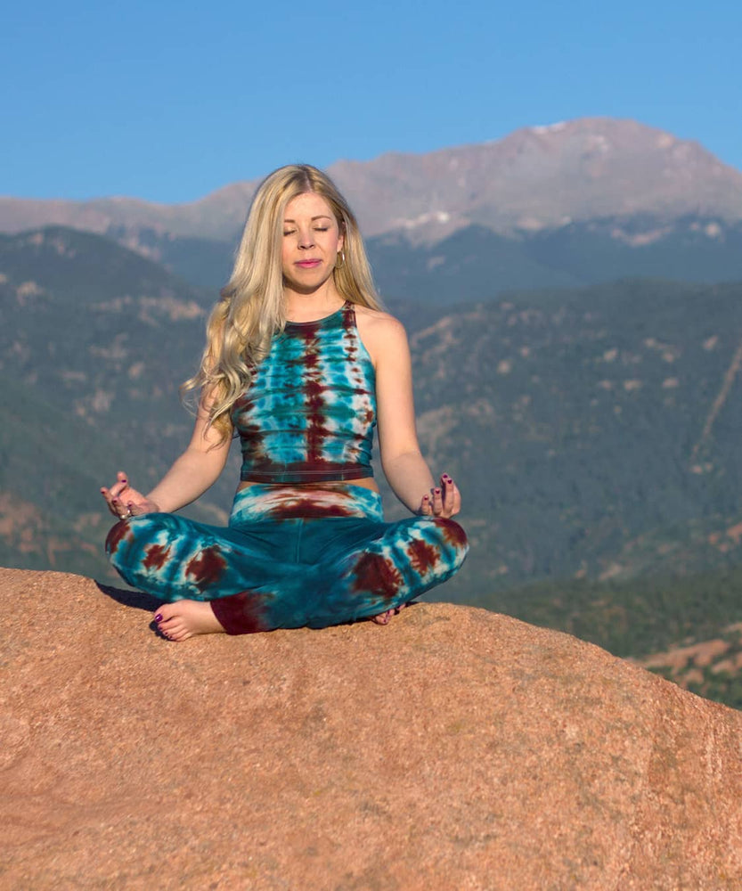 Woman standing in Garden of the Gods wearing Kiowa tie dye yoga pants with a fold over waistband in the colors teal and copper.