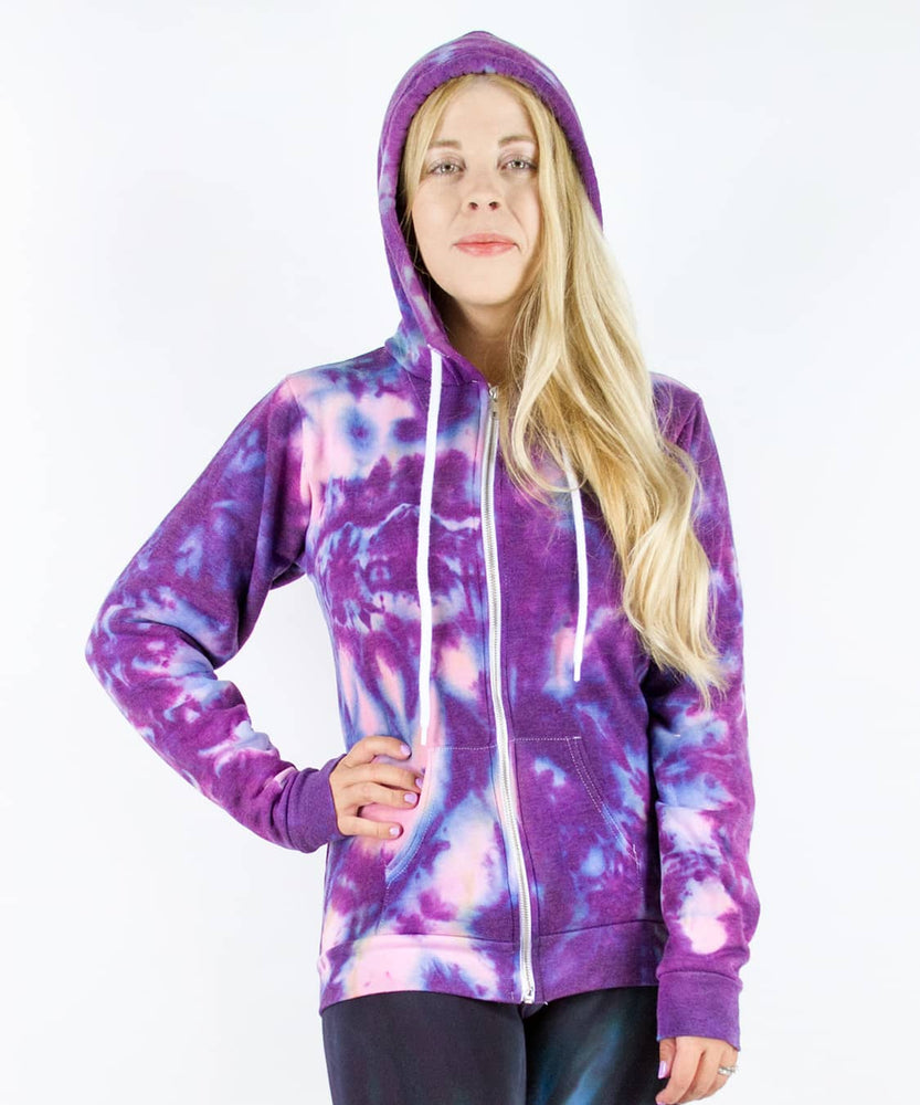 Woman wearing a purple and pink tie dye hoodie jacket with a zipper.