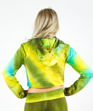 Woman wearing a tie dye hoodie crop top in green, yellow, and teal by Akasha Sun.