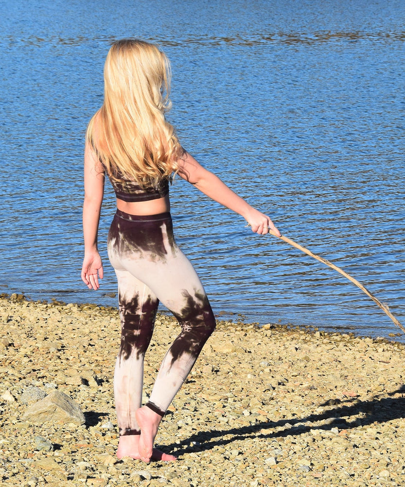 Woman wearing a pair of tie dye leggings by Akasha Sun in the colors cream and dark brown.