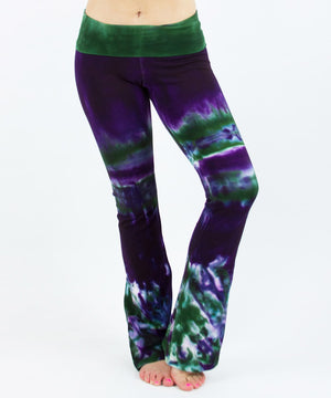 Woman wearing a pair of purple and green tie dye yoga pants with a fold over waistband by Akasha Sun.