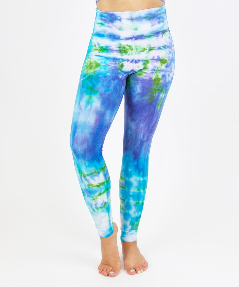 Woman wearing the Grenada tie dye leggings that feature a fold over waistband.  The colors of the leggings include aqua, lavender, and emerald.