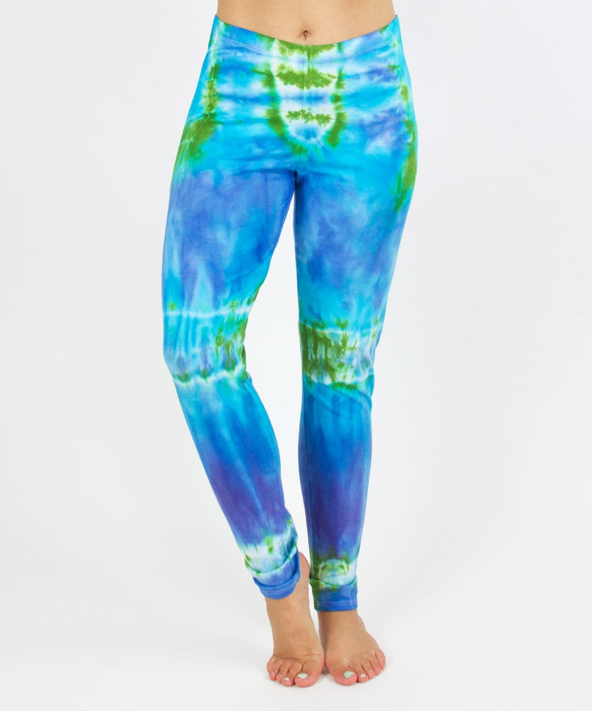 Woman wearing the Grenada tie dye leggings that feature hues of aqua, lavender, and emerald.