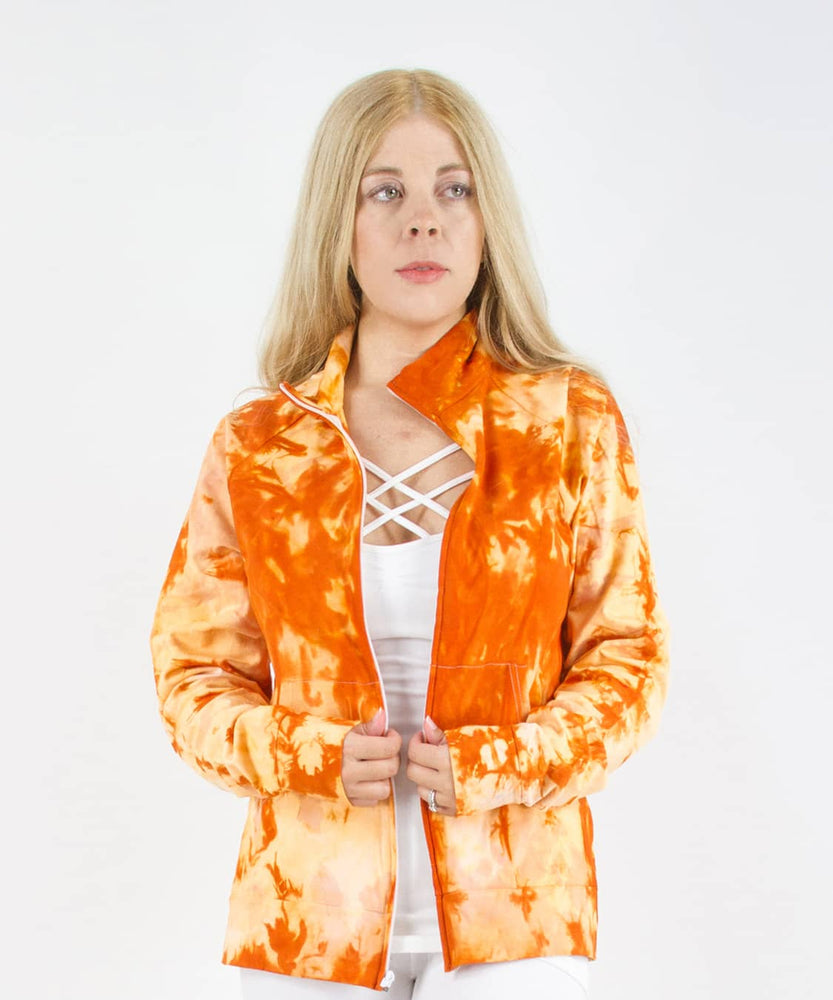 Woman wearing an orange tie dye jacket in a cadet style with zipper and pockets.