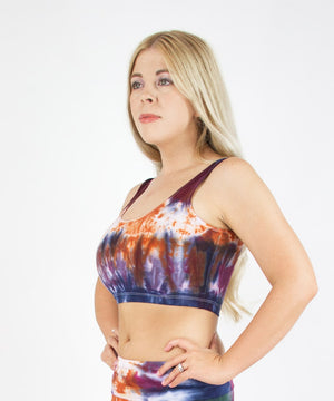 Woman wearing the Meteorite tie dye crop tank featuring a scoop neckline.  The colors in the crop top are orange, navy blue, purple, and dark green.