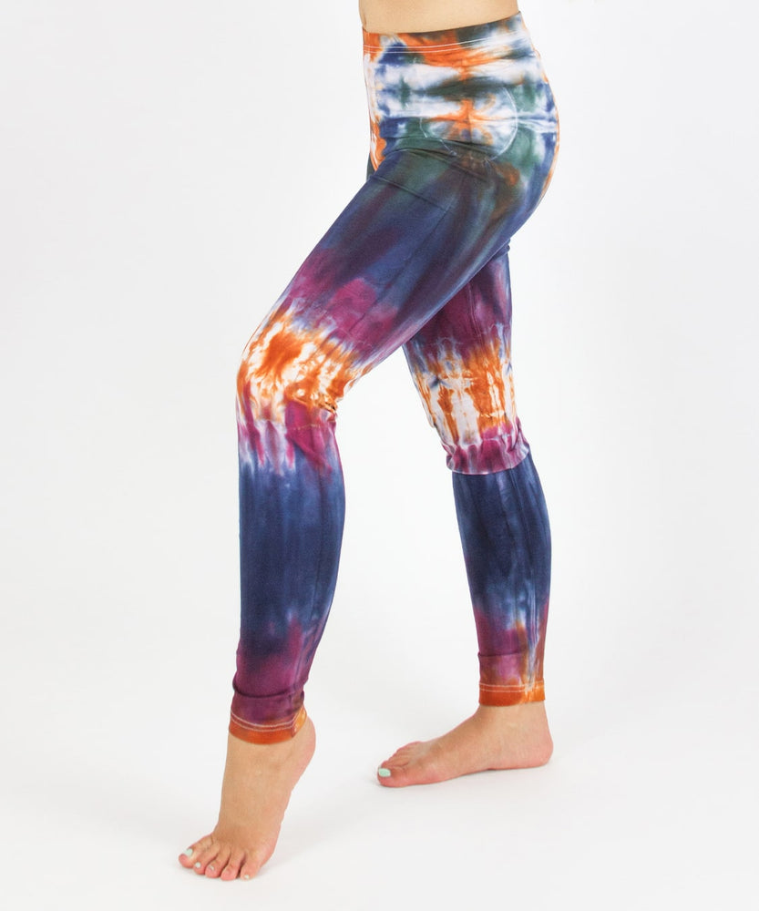 Woman wearing the Meteor tie dye leggings that feature the hues orange, navy, purple, and green.