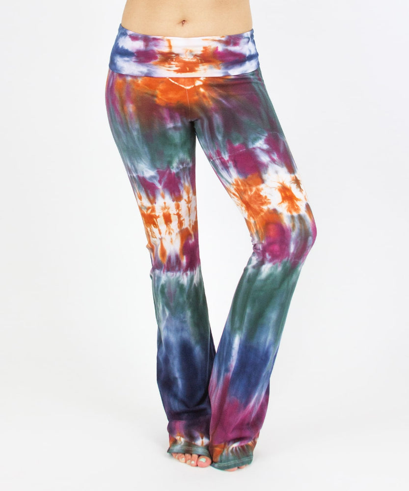 Woman wearing the Meteor tie dye yoga pants that feature a fold over waistband.  The colors in these pants include orange, purple, green, and navy blue.
