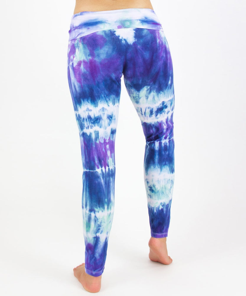 Woman wearing the Mykonos tie dye leggings featuring a fold over waistband.  The colors in the pants include blue, light teal, purple, and white.
