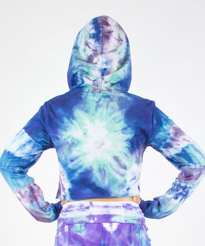 Woman wearing the Mykonos tie dye hoodie crop top featuring an oversized hood, drawstrings, and raw edge.  The colors in the crop top include blue, light teal, purple, and white.