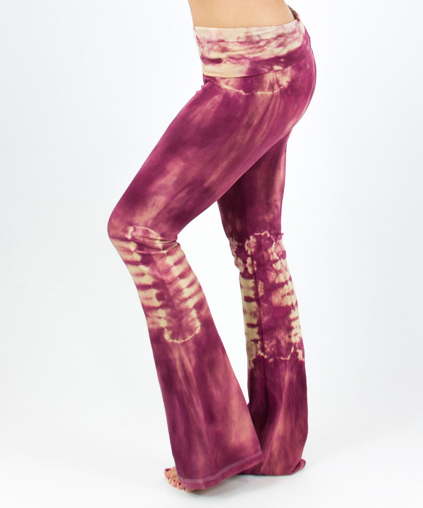Woman wearing a pair of rose pink tie dye yoga pants with a fold over waistband by Akasha Sun.