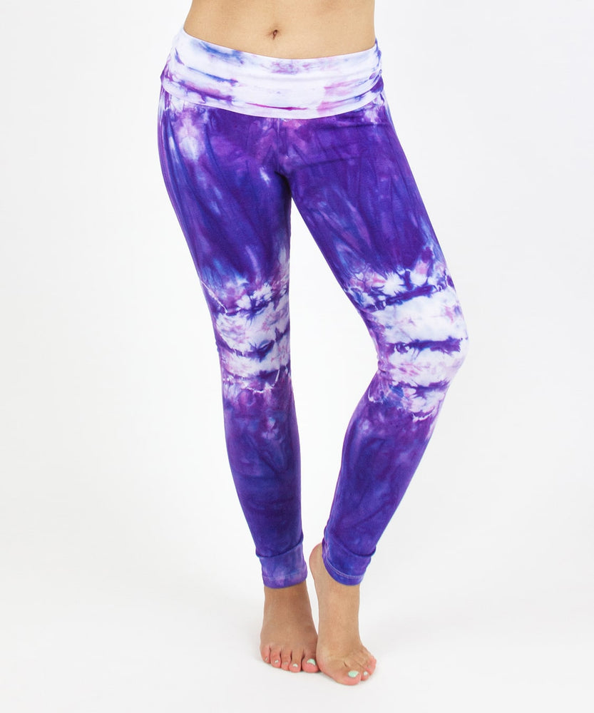 Woman wearing the Saint-Tropez tie dye leggings that feature a fold over waistband.  The colors in these pants include purple, pink, and white.