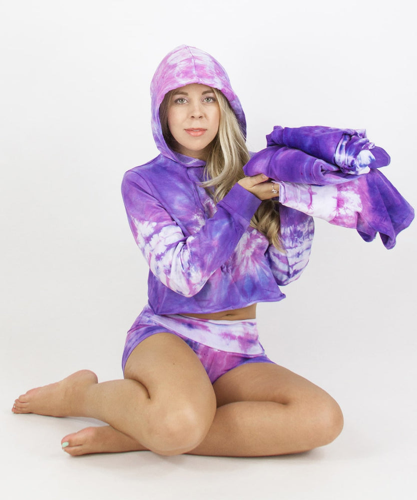 Load image into Gallery viewer, Woman wearing the Saint-Tropez tie dye hoodie crop top.  It features a hood, drawstrings, and a raw edge.  The colors in the top are purple, pink, and white.
