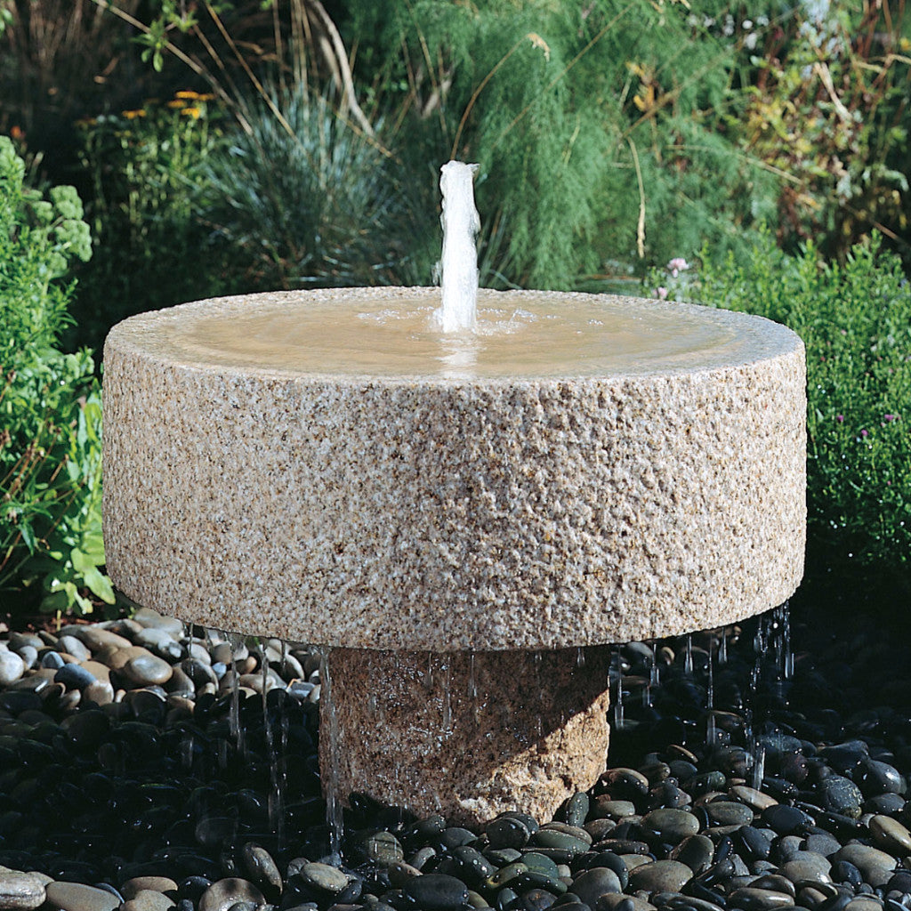 Rough millstone fountain in our outdoor garden