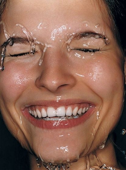 Smiling woman's face rinsed with water