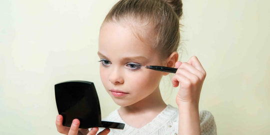 Young Girl Applying Makeup while Holding Compact Mirror