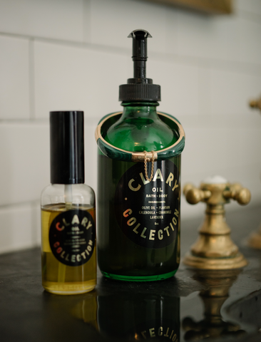 Regular and Travel Size Clary Bath and Body Oil on Bathroom Sink