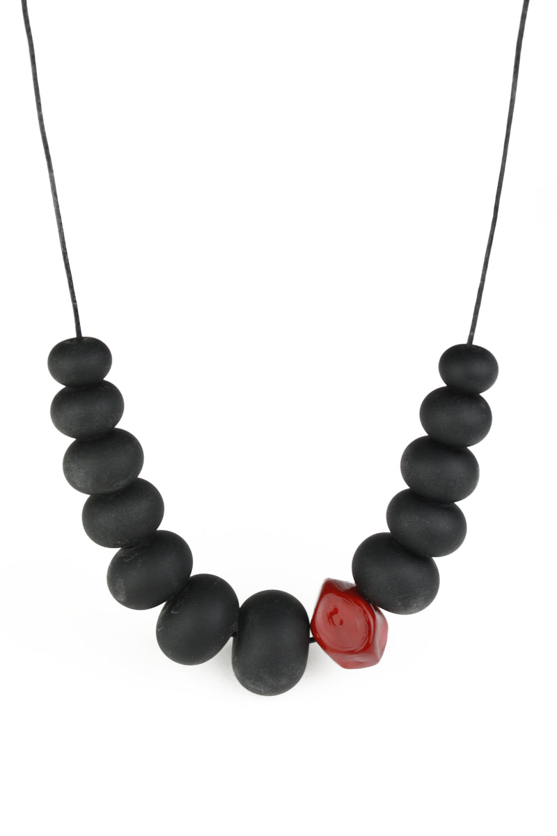 Necklace of hand blown and sandblasted hollow beads in velvety black glass paired with a red glass nugget bead and strung on adjustable leather
