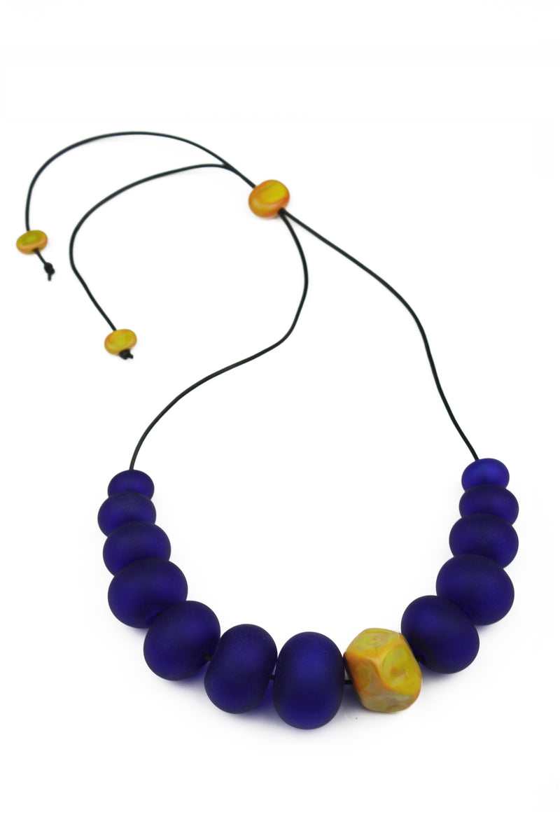Necklace of hand blown and sandblasted hollow beads in cobalt blue glass paired with a ochre yellow glass nugget bead and strung on adjustable leather
