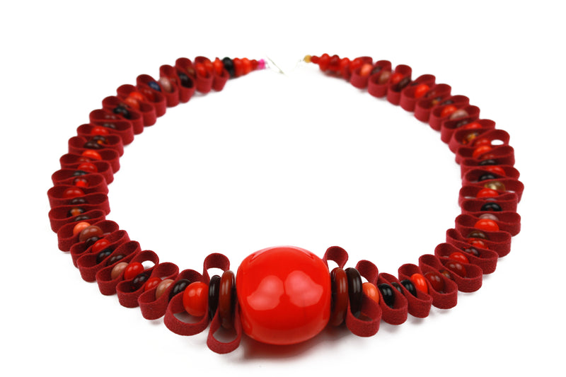 Hand crafted glass beads in shades of red, orange, amber and plum are interspersed with a velvety soft red ribbon.