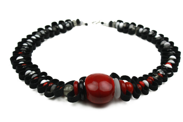 Hand crafted glass beads in shades of black white and red are interspersed with a velvety soft black ribbon.