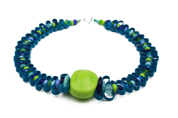 Hand crafted glass beads in shades of blues and greens are interspersed with a velvety soft bright blue ribbon.