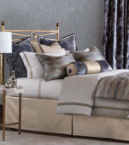 Imogen dazzles in the timeless appeal of precious metals. Its textured gray duvet cover and distressed-velvet Euro shams provide the perfect backdrop for its shimmering main fabric, a wavy and lustrous textile in a range of metallic and stony hues. Tassels and silvery-gold ruffles add an extra dimension of eye-catching and sophisticated luster