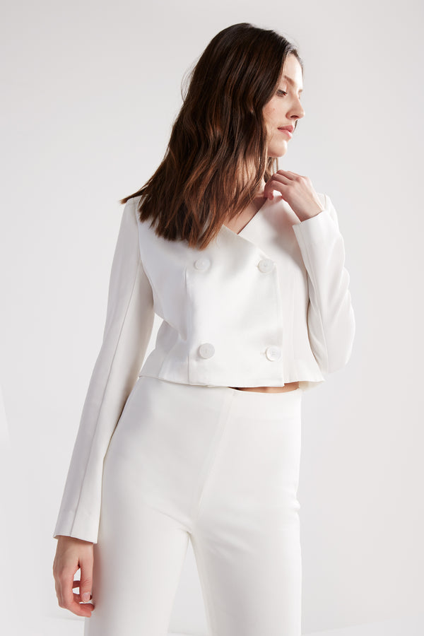 Cropped, double-breasted, collarless blazer with full length sleeves. Made in a white matte and satin fabric.