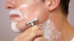 Image of a man using a stainless steel double edge safety razor