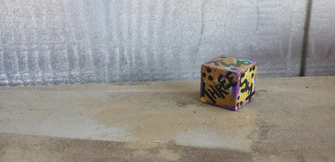 A photo of a single, painted d6 with written numbers, against a white wooden background