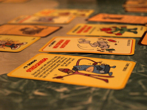 A close up photograph of several Munchkin cards, laid out as though the photographer is in the middle of playing a game of Munchkin