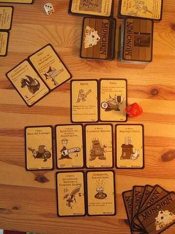 A photo of a table, on which are spread several cards for the game of Munchkin in the original edition